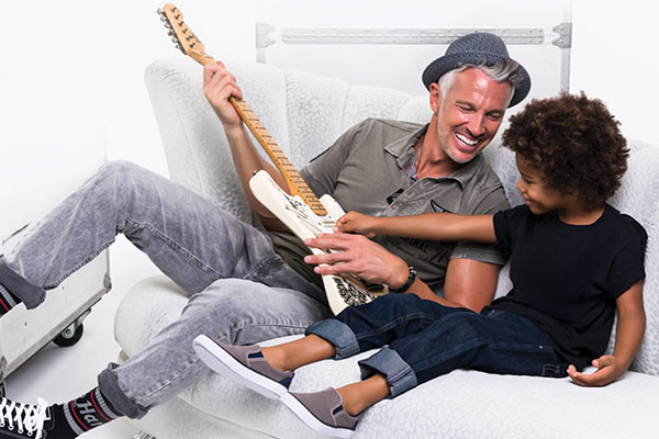 Dad playing guitar with his son