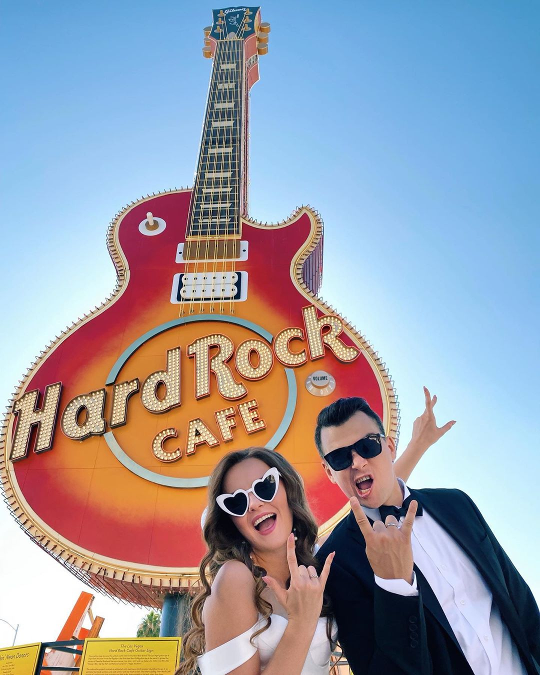 Photo of a Hard Rock guitar sign with a married couple wildly posing in front.